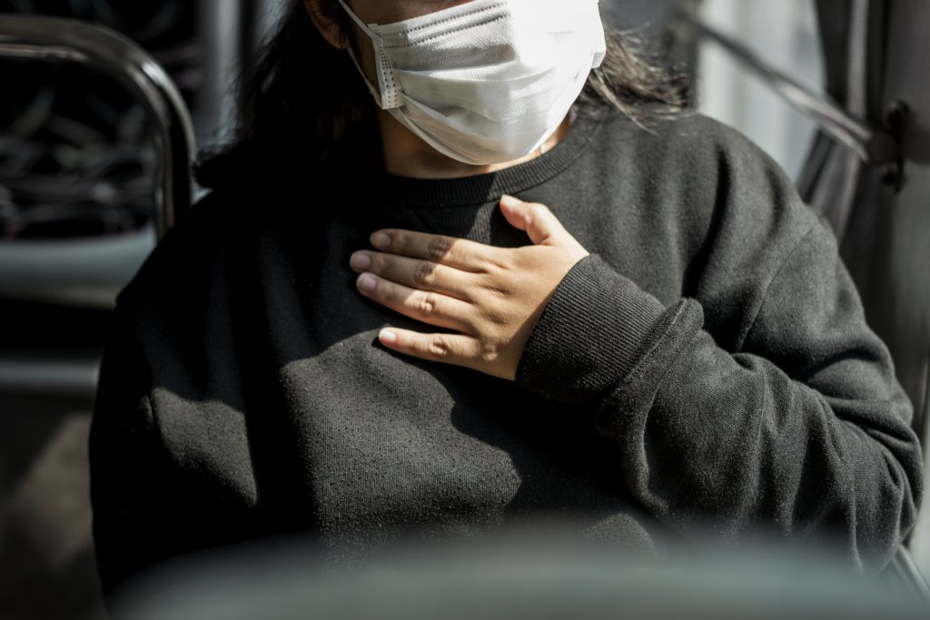sick woman mask having difficulty breathing during coronavirus pandemic